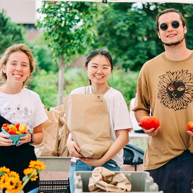 People at farmers market with produce.