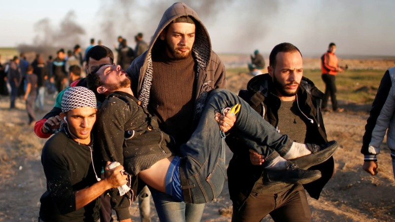 A wounded Palestinian is evacuated during clashes with Israeli troops during a protest on the Israel-Gaza border.