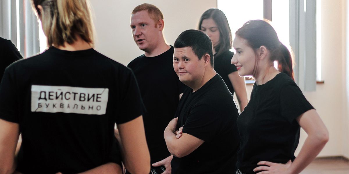 Members of a theater group wearing black shirts at a rehearsal