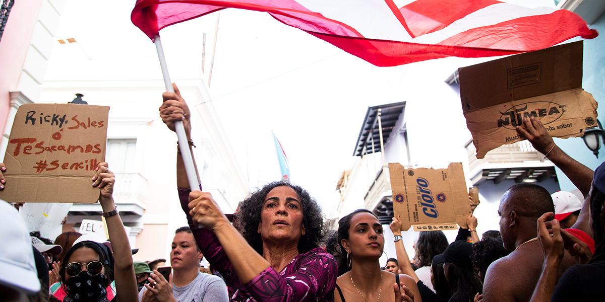 A woman holding a Puerto Rican flag among other protestors