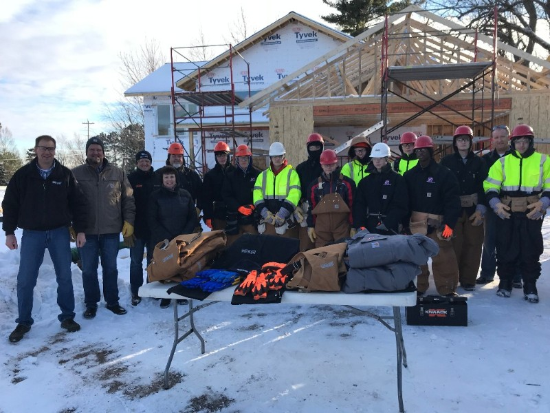 Scott Kyrola with Northland Constructors, Mel Olson with United Piping, Inc., Craig Fellman with The Jamar Company, Sandy Johnson with APEX, Tony Leone with ISD 709, a group of students wearing their new gear and Brad Vieths with ISD 709