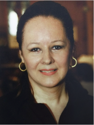 DESCRIÇÃO DA FOTO 3x4: Ika é uma mulher branca, com aproximadamente 60 anos e está sorrindo. Seu cabelo castanho escuro e liso está preso e ela usa um brinco de argola. Ela veste uma blusa preta.