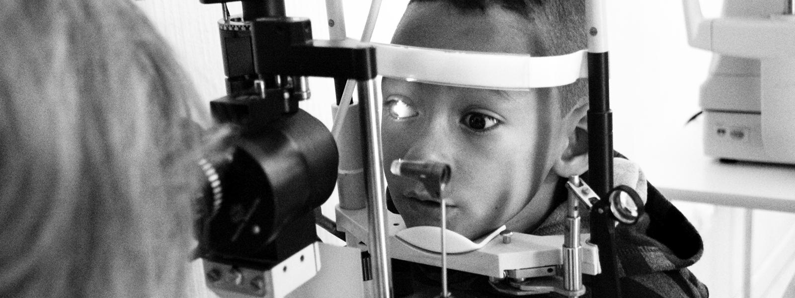 DESCRIÇÃO DE IMAGEM: Foto em preto e branco com destaque para menino de cerca de 10 anos sendo examinado por uma mulher de cabelo claro. Ele apoia o queixo em um aparelho oftalmológico enquanto seu olho direito está iluminado.