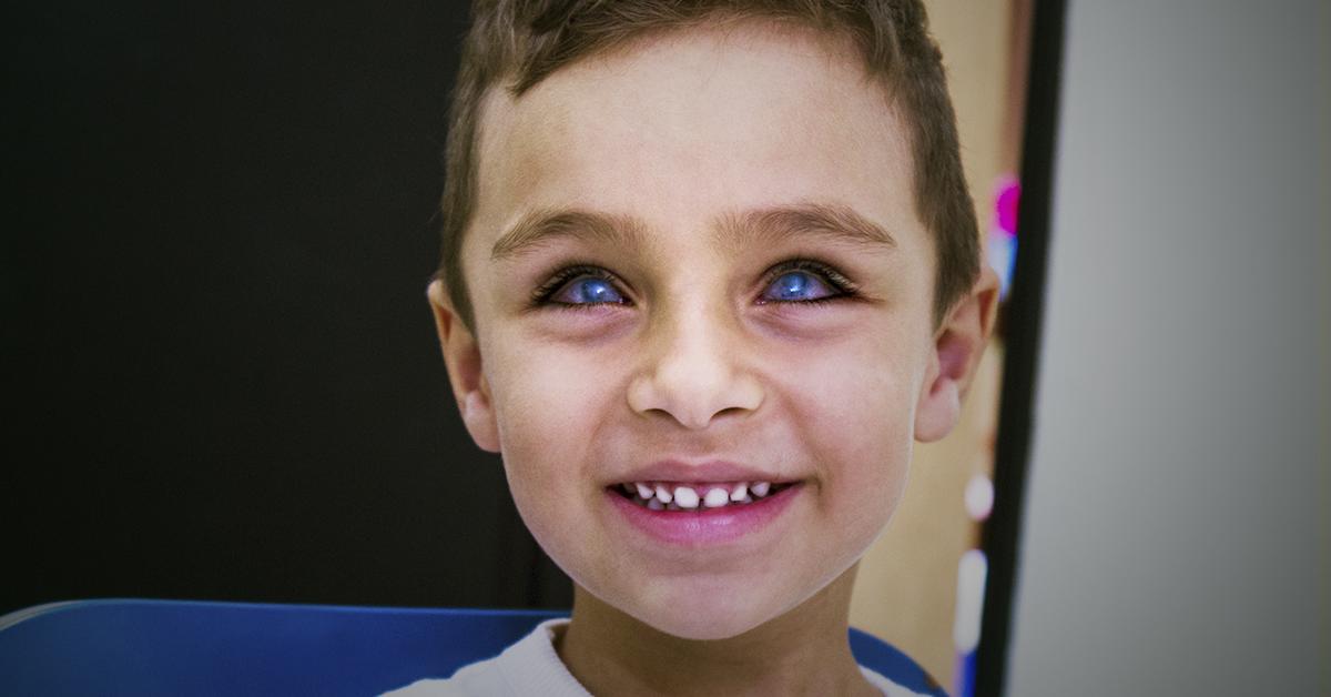 DESCRIÇÃO DA IMAGEM: Foto retangulare com fundo escuro, embaçado. Em primeiro plano, um menino branco, de cerca de 5 anos, sorri olhando para câmera. Seus olhos são azulados e possui cabelos castanhos curtos.