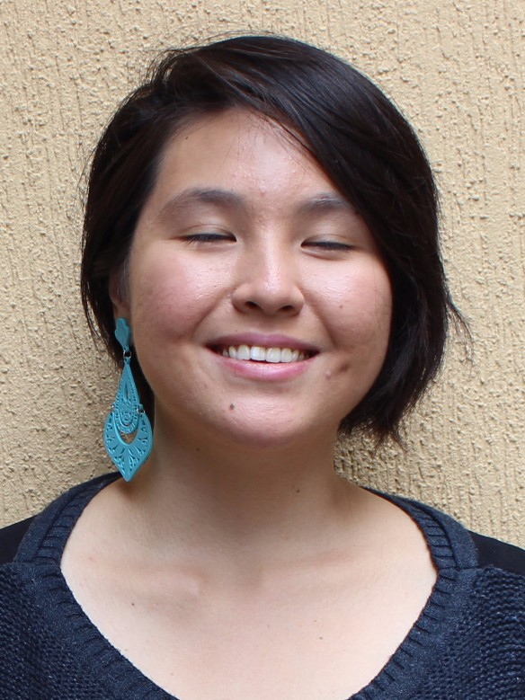 DESCRIÇÃO DA FOTO 3x4: Marina é uma garota oriental, com pouco mais de 20 anos e está sorrindo e de olhos fechados. Seu cabelo preto e liso contorna o rosto sem ultrapassar o pescoço e ela usa um brinco azul em formato de losango na orelha direita. Ela veste uma blusa azul escuro e está encostada em uma parede bege.