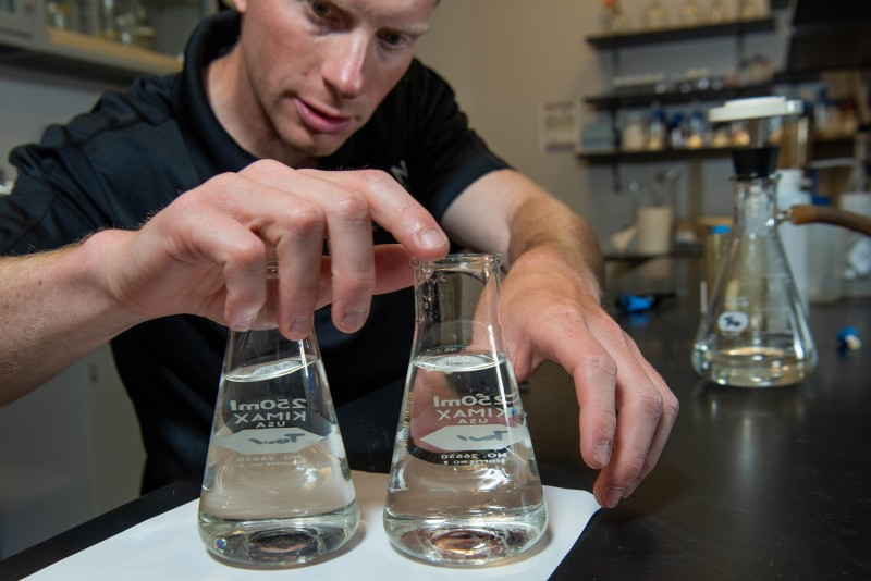Researcher working with flasks of water in a laboratory