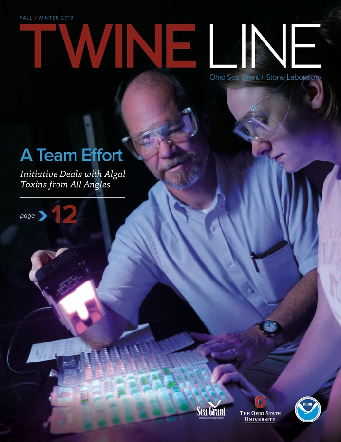 "The cover of Twine Line magazine showing researchers shining a light onto test tubes and the title ""A Team Effort"""