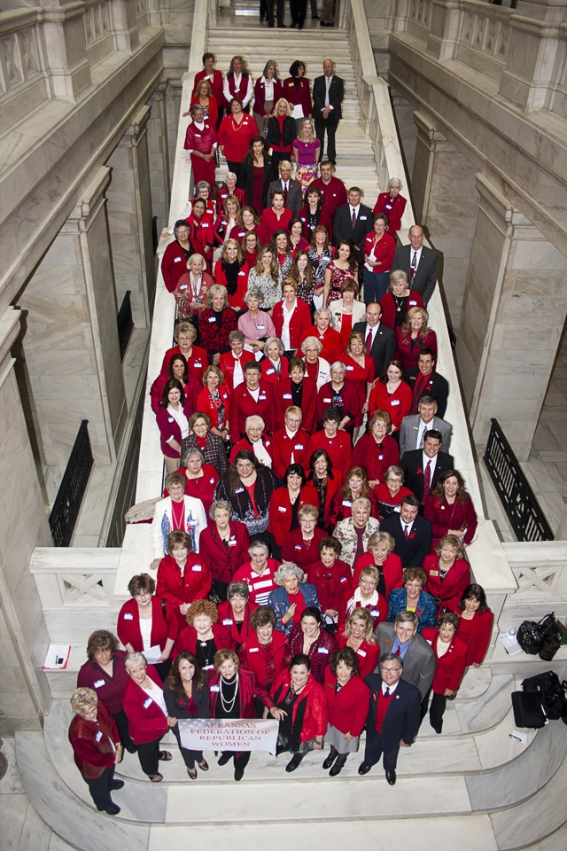 """Dressed in """"Republican Red,"""" attendees take a group photograph with Republican representatives and senators on the Capitol grounds."""