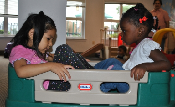 two toddlers sitting in a box