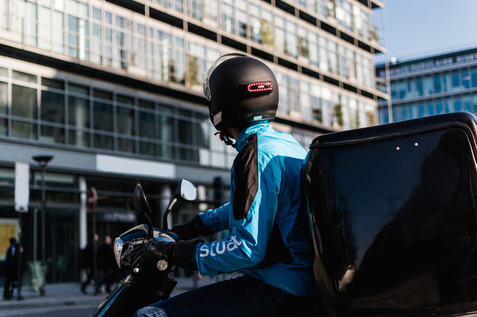 A Stuart's delivery driver wearing a Cosmo Connected's rear light on his helmet