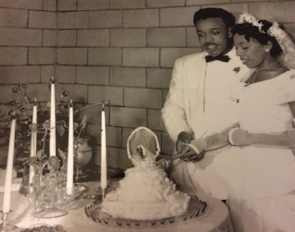a black and white photo. An African American man and woman in wedding attire cutting a wedding cake.