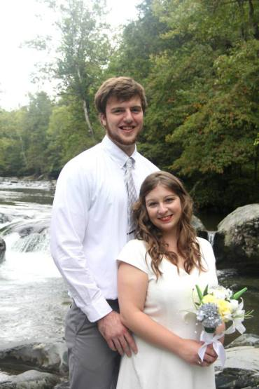 Brunette woman and tall man in wedding clothes smiling at the camera.