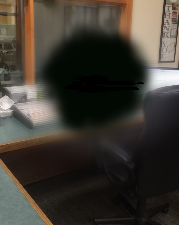 A radio studio, distorted with a big, black circle in the middle
