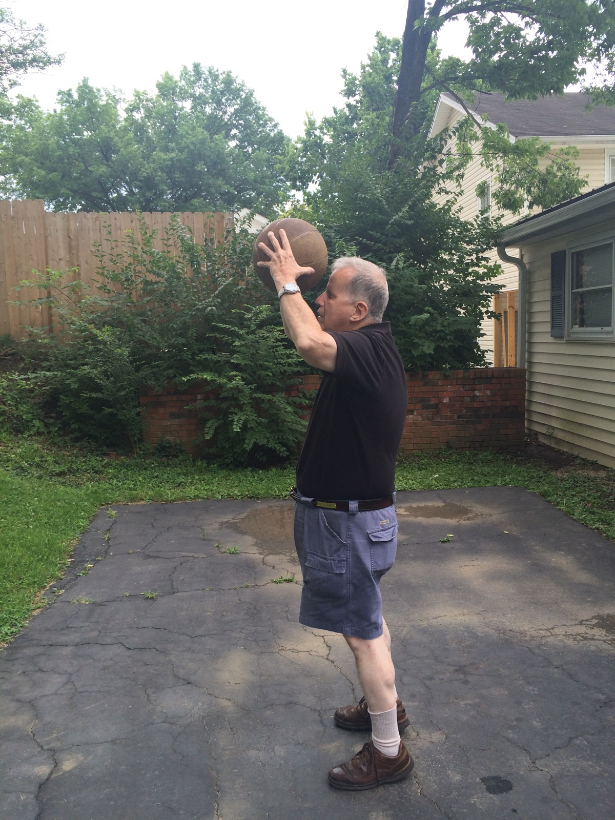 Man in a black t-shirt and jean shorts holding a basketball to his head, arms above his head.