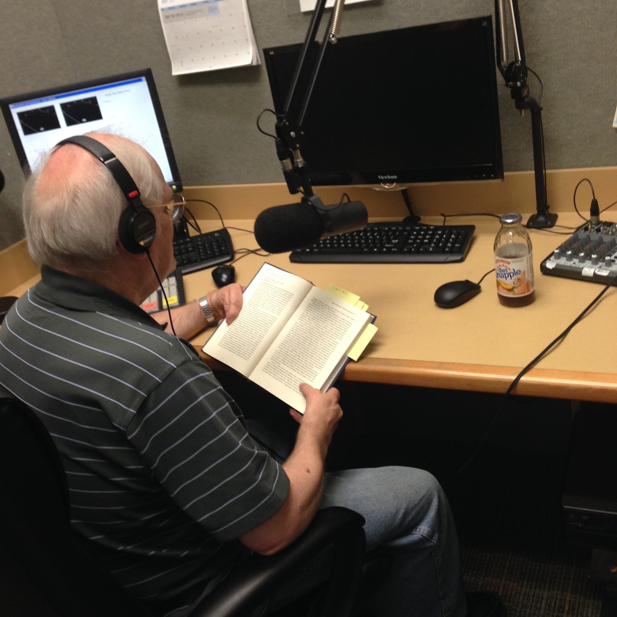 White haired man in gray and white striped shirt reading a book in a recording booth.