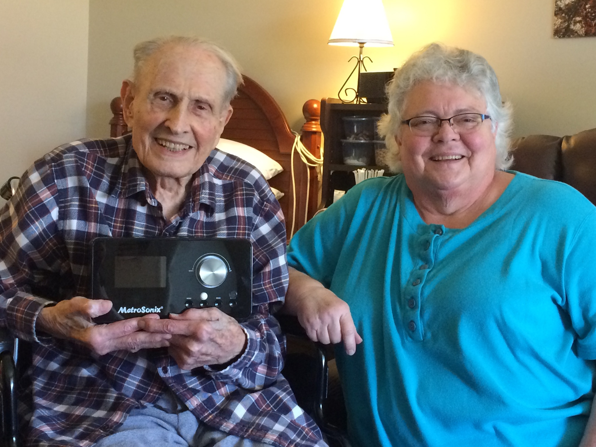 Older man in plaid shirt holds a radio. To his right, sits a lady in a blue shirt.