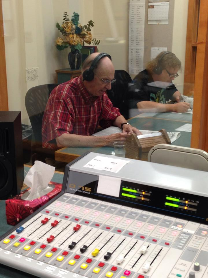Older man wearing a microphone headset reads the newspaper next to a younger man with long hair. Control board in the foreground.