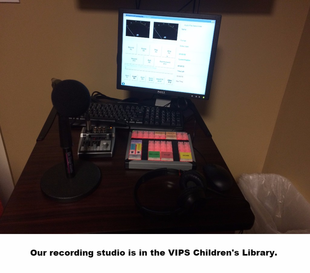 broadcast equipment - microphone in foreground, keypad with red backlighting in midground, recording computer in back, all on a brown table. Caption says: Our recording studio is in the VIPS Children's Library.