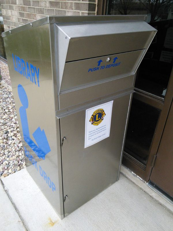 Tall silver dropbox with library logo and Lions Club flyer on it