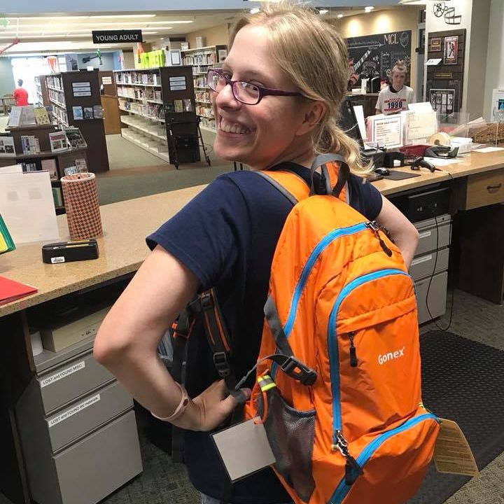 Woman wearing orange backpack in library