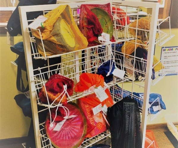 Tower shelving of games in colored mesh bags