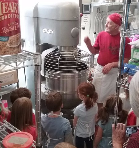 Baker showing kids a giant mixer in the kitchen