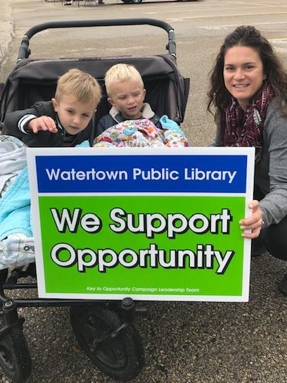 "Woman kneeling next to stroller with two boys in it. She holds sign that reads ""Watertown Public Library We Support Opportunity"""
