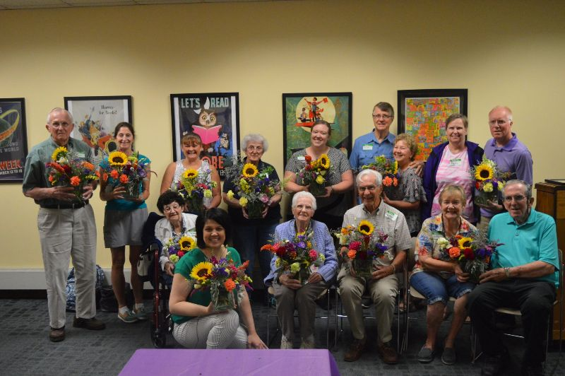 Group of senior citizens and librarians pose for the camera, holding bouquets of flowers