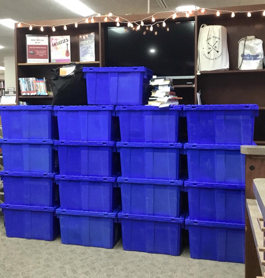 Tall stack of blue bins in front of a library shelf