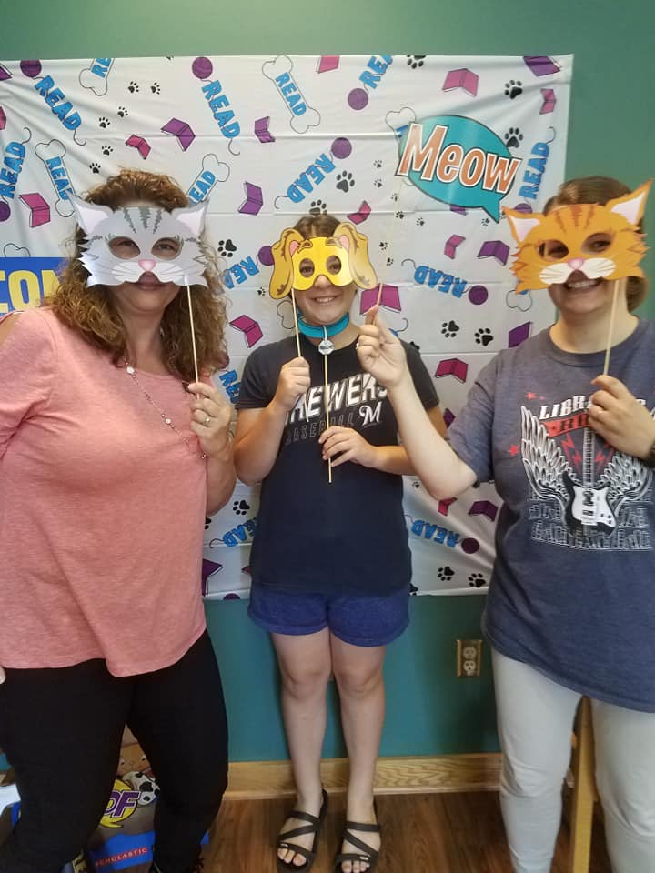 Three people hold cat and dog masks attached to sticks up to their faces.
