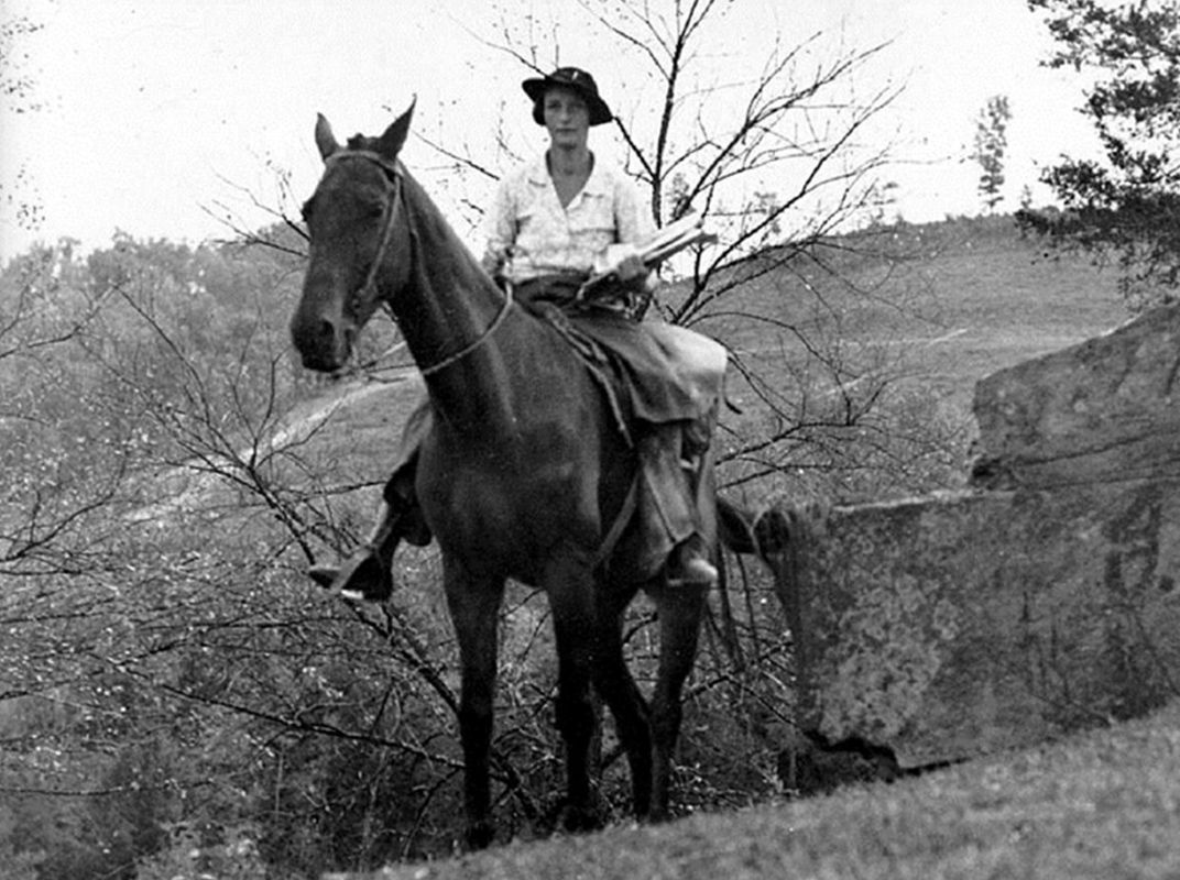 Vintage photograph of young woman holding books, sitting on a horse