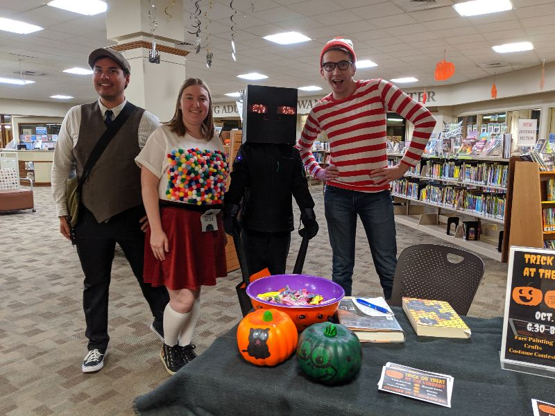 Group of librarians in costumes standing in library next to table filled with candy and pumpkins