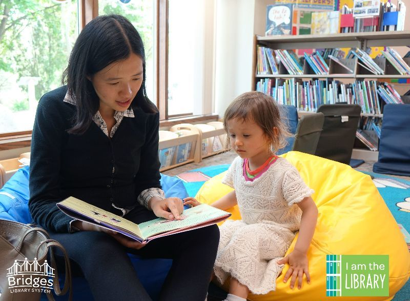 Woman reads to little girl, sitting on beanbag chairs