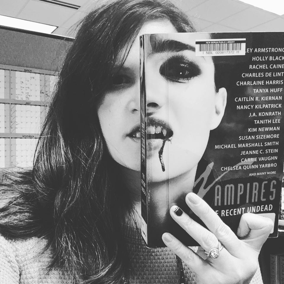 Woman holding vampire book up to her face.