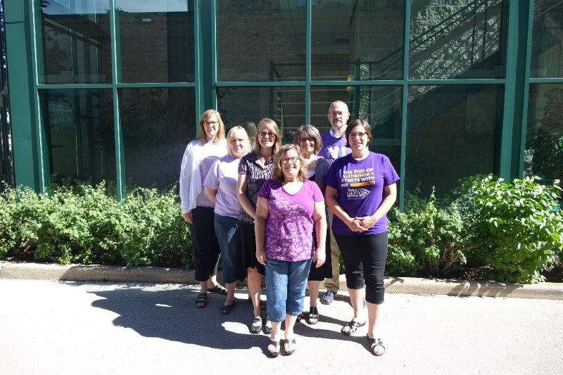 Seven staff members wearing purple shirts and standing outside of a building