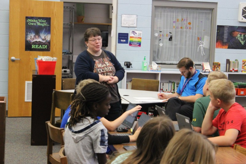Woman speaking to several elementary school students sitting at desks.