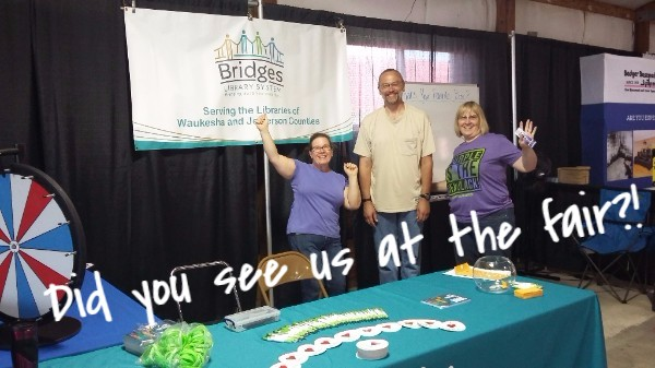 """Shawn, Mellanie, and Meg standing at the Jefferson County fair booth. The photo has a caption that reads """"Did you see us at the fair?!"""""""