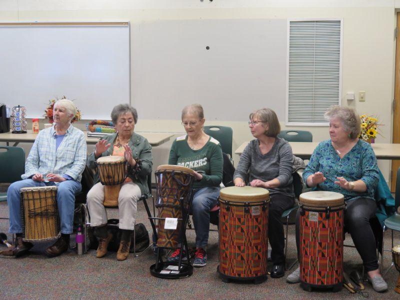 Five senior women sitting in a row, drumming on large bongo drums
