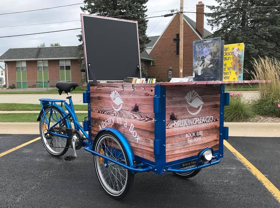 A modified bicycle with a large cart at the back and several books standing on top of the cart. Bike is in a parking lot.