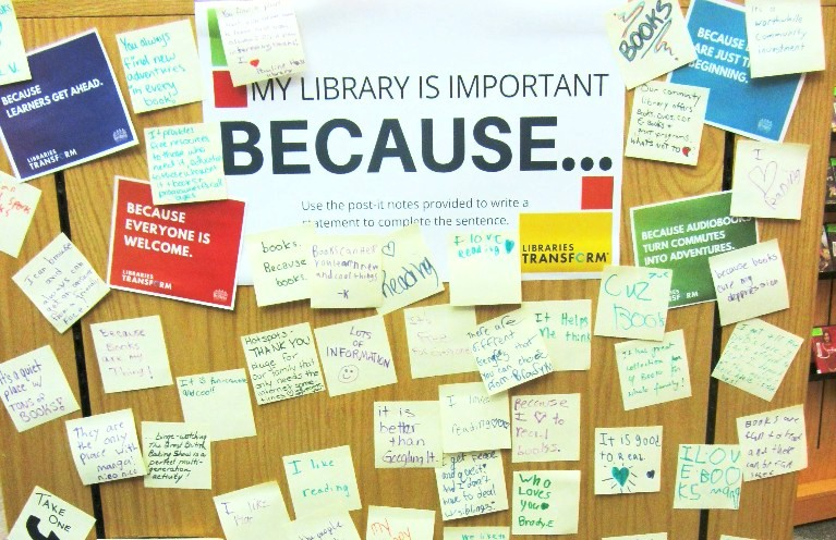 "A bulletin board of handwritten post-it notes surrounding a sign that reads ""My Library Is Important Because...."""