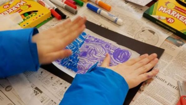 Child's hands work on a piece of colored paper.