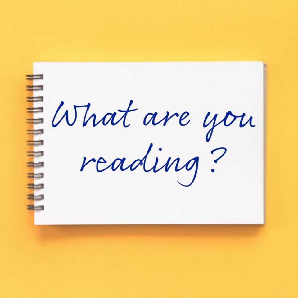 """White notebook page against yellow background with writing on it. Text reads: """"What are you reading?"""""""