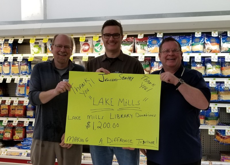 Three men standing in grocery store holding sign declaring a donation to L.D. Fargo Library