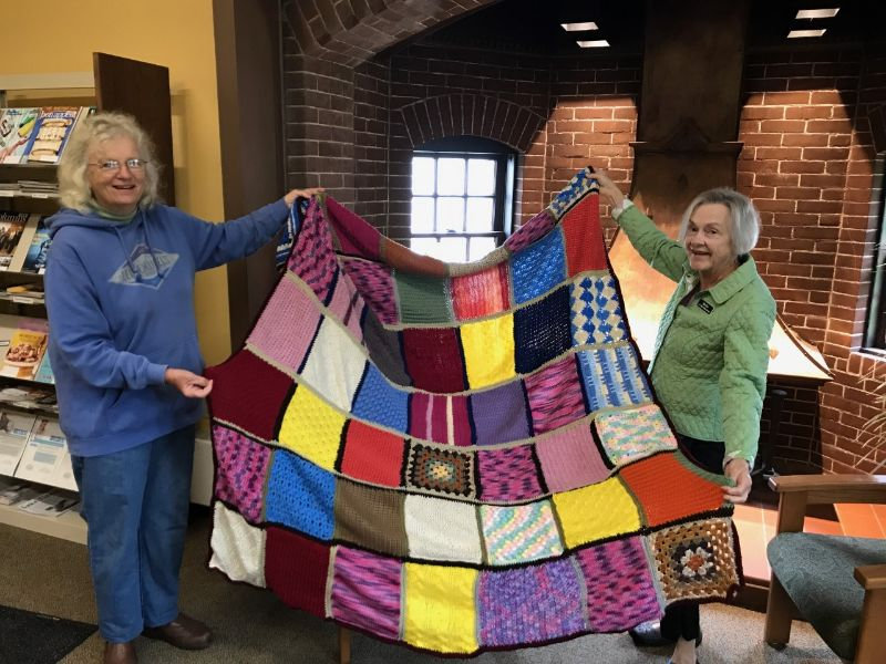 Two women hold out a colorful afghan blanket