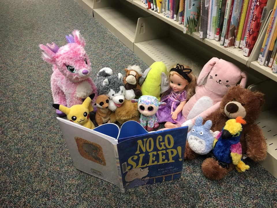 Group of dolls and stuffed animals sitting on floor next to a book