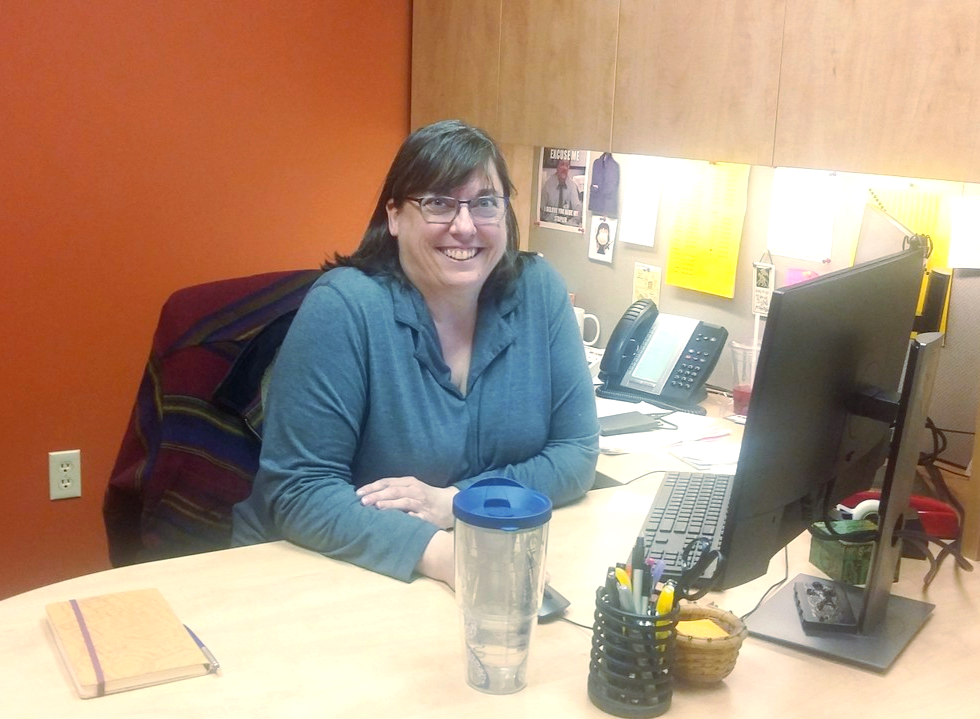 Woman sitting at desk and smiling at camera
