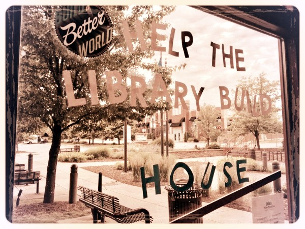"""Window with a sign that says """"Help the library build a house"""""""