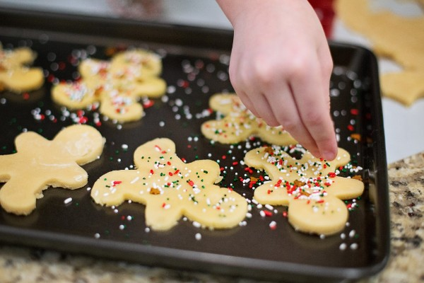 Child's hand sprinkling sprinkles on cut-out Christmas cookies