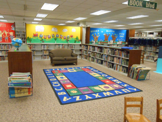Muskego Public Library children's area, with bookshelves, bulletin boards, and alphabet rug