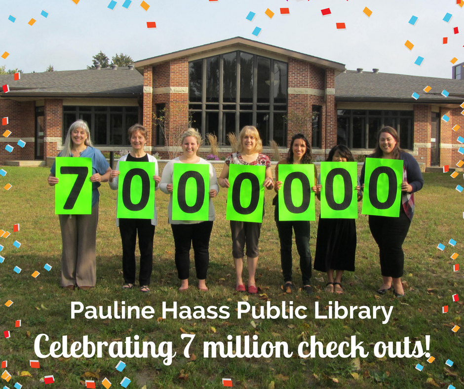 """Librarians standing in front of library holding signs with the numbers """"7,000,000"""""""